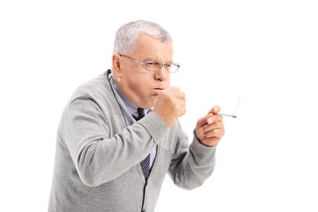 Senior smoking a cigar and coughing isolated on white background 스톡 콘텐츠