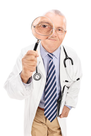 Mature doctor looking through a magnifying glass isolated on white background