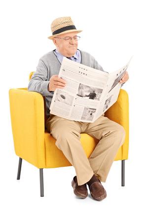 Vertikale Schuss von einem leitenden Lesen einer Zeitung in einem modernen Sessel isoliert auf weißem Hintergrund