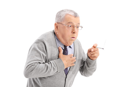 man smoking: Senior man choking from the smoke of a cigarette isolated on white background Stock Photo