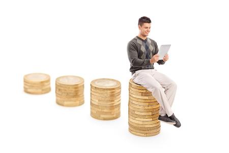 hombre sentado: Hombre trabajando en una tableta sentado en la pila de monedas aisladas sobre fondo blanco Foto de archivo