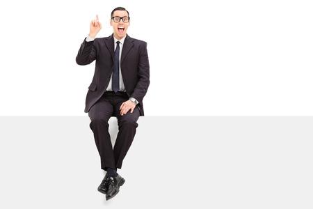 若いビジネスマンが白い背景で隔離されたパネルに装着されているアイデアを持ってください。
