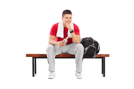 Handsome sportsman sitting on a wooden bench isolated on white background photo