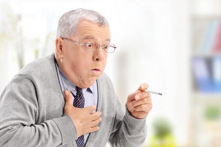 persona fumando: Hombre mayor de asfixia por el humo de un cigarrillo en el hogar