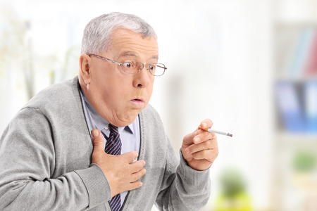 smoking issues: Senior man choking from the smoke of a cigarette at home