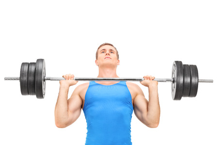 Young weightlifter training with a heavy barbell isolated on white background photo