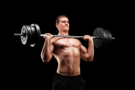 Determined athlete lifting a heavy weight on black background