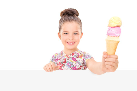 Little girl holding an ice cream behind billboard isolated on white background photo