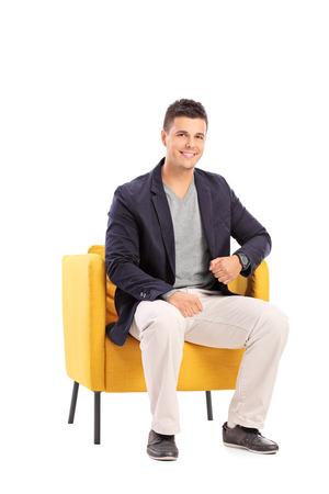 hombre sentado: Sonriente hombre sentado en una silla moderna aislada en el fondo blanco