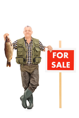 "Full length portrait of a smiling mature fisherman holding a fish next to a panel noted ""For sale"" isolated on white background photo"