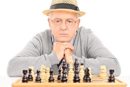 jugando ajedrez: Mayor que comtempla su próximo movimiento en juego de ajedrez aisladas sobre fondo blanco Foto de archivo