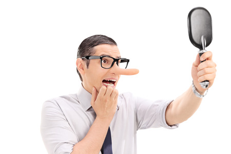dishonest: Scared man with long nose looking in a mirror isolated on white background