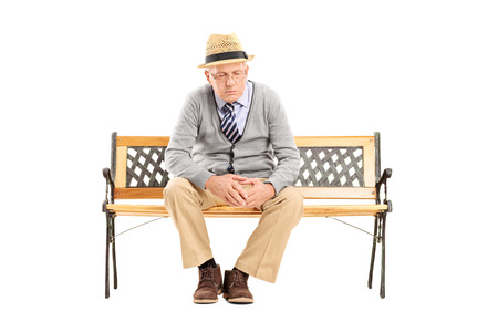 sit studio: Sad senior thinking seated on a bench isolated on white background