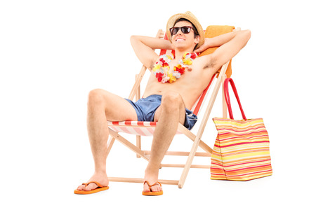 beachwear: Young man enjoying seated in a sun lounger isolated on white background