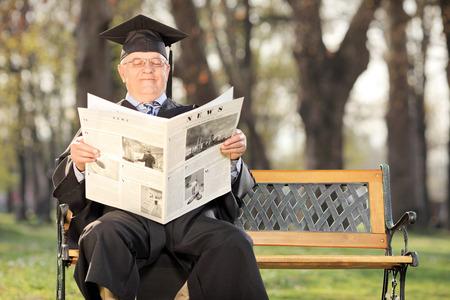 director de escuela: Profesor de la universidad madura que lee las noticias en el parque sentado en un banco