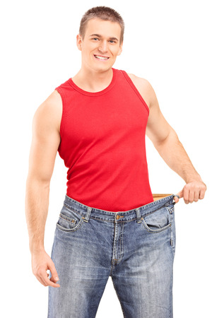 oversized: Happy guy posing in a pair of oversized jeans isolated on white background