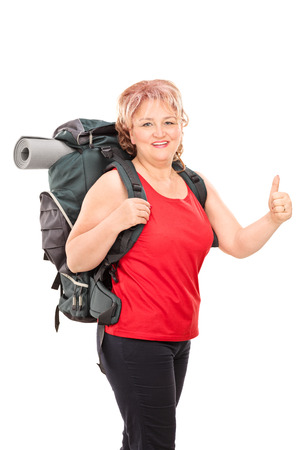 mat like: Vertical shot of a mature lady with hiking equipment giving thumb up isolated on white background Stock Photo