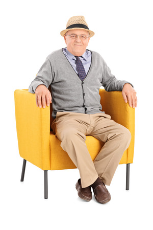 man in chair: Senior sitting in a modern armchair and looking at camera isolated on white background