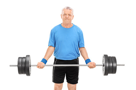 Mature man lifting a heavy barbell isolated on white background photo