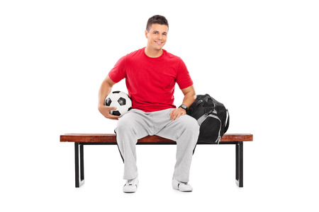 player bench: Young football player sitting on a bench isolated on white background