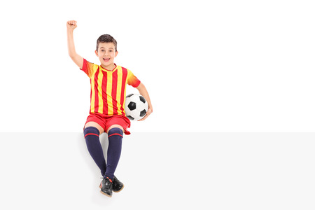 junior soccer: Junior soccer player gesturing joy seated on a panel isolated on white background