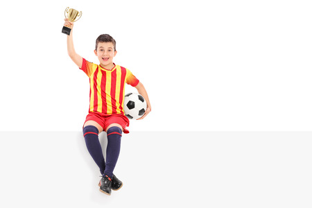 Junior football player holding a trophy on a panel isolated on white background photo