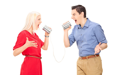 tin can phone: Couple arguing through a tin can phone isolated on white background