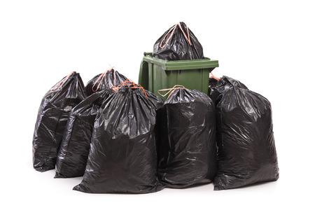 Prullenbak omringd door een bos van vuilniszakken op een witte achtergrond Stockfoto