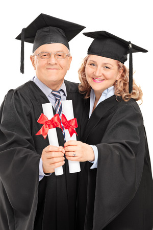 Mature couple in graduation gowns holding diplomas isolated on white background photo
