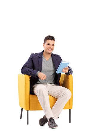 hombre sentado: Tiro vertical de un hombre que sostiene un libro sentado en un sillón aislado en fondo blanco