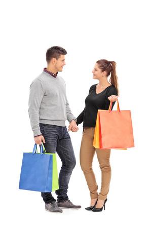 dos personas hablando: Retrato de cuerpo entero de una pareja joven con bolsas de la compra que tienen una conversaci�n aislada en el fondo blanco