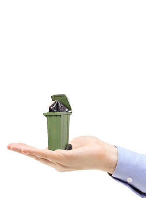 Vertical studio shot of a Caucasian hand holding a green trash can isolated on white background photo