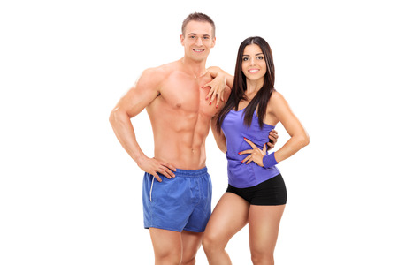 An athletic young couple posing together isolated on white background photo