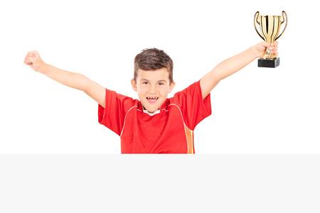 niños con pancarta: Junior Alegre celebración de un trofeo detrás de un panel aislado en el fondo blanco Foto de archivo
