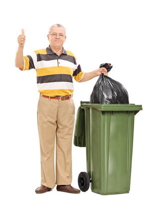 Full length portrait of a senior giving a thumb up by a trash can isolated on white background