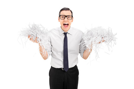 shred: Terrified man holding a bunch of shredded paper isolated on white background
