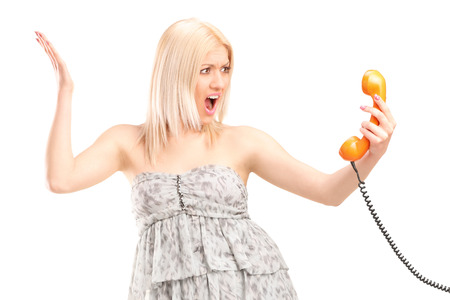 angry blonde: Angry woman holding a telephone speaker isolated on white background