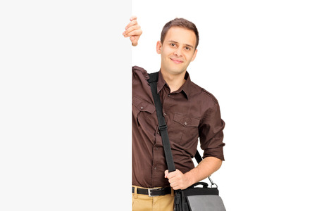 Young male student standing behind a panel isolated against white background photo