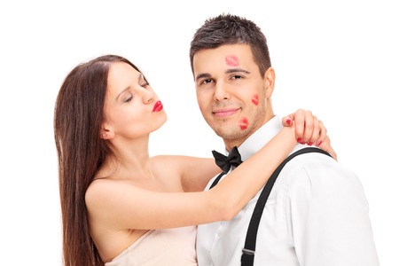 lipstick kiss: Girl covering a young man in kisses isolated on white background