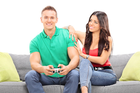 Girl watching her boyfriend play video game seated on a sofa isolated against white background photo