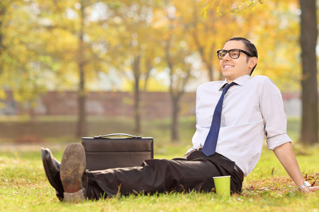 Businessman relaxing seated on the grass in park photo