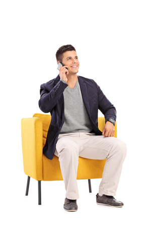 hombre sentado: Hombre hablando por un teléfono sentado en un sillón moderno aislado en el fondo blanco Foto de archivo