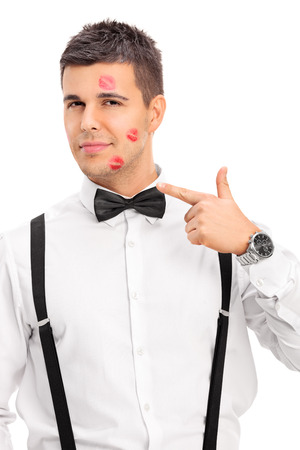 lipstick kiss: Vertical shot of a man covered in lipstick kiss marks isolated on white background