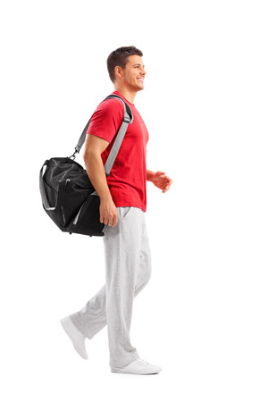 sports equipment: Full length portrait of a male athlete walking with a sports bag isolated on white background Stock Photo