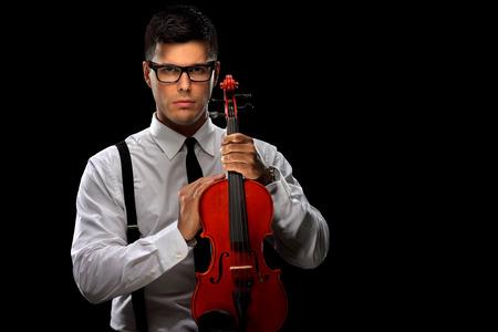 Jonge muzikant poseren met een viool op zwarte achtergrond Stockfoto