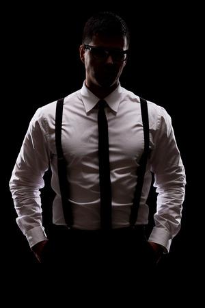 Verticale shot van een mysterieuze man die in het donker op zwarte achtergrond