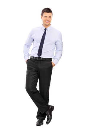 Full length portrait of a casual young businessman leaning against a wall isolated on white background photo