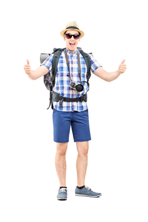 posing  agree: Full length portrait of a young tourist giving thumbs up isolated on white background Stock Photo