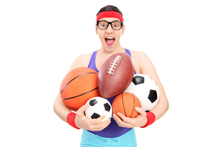 nerdy: Nerdy guy holding a bunch of sports balls isolated on white background