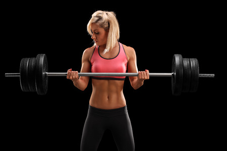 Attractive female athlete exercising with barbell on black background photo